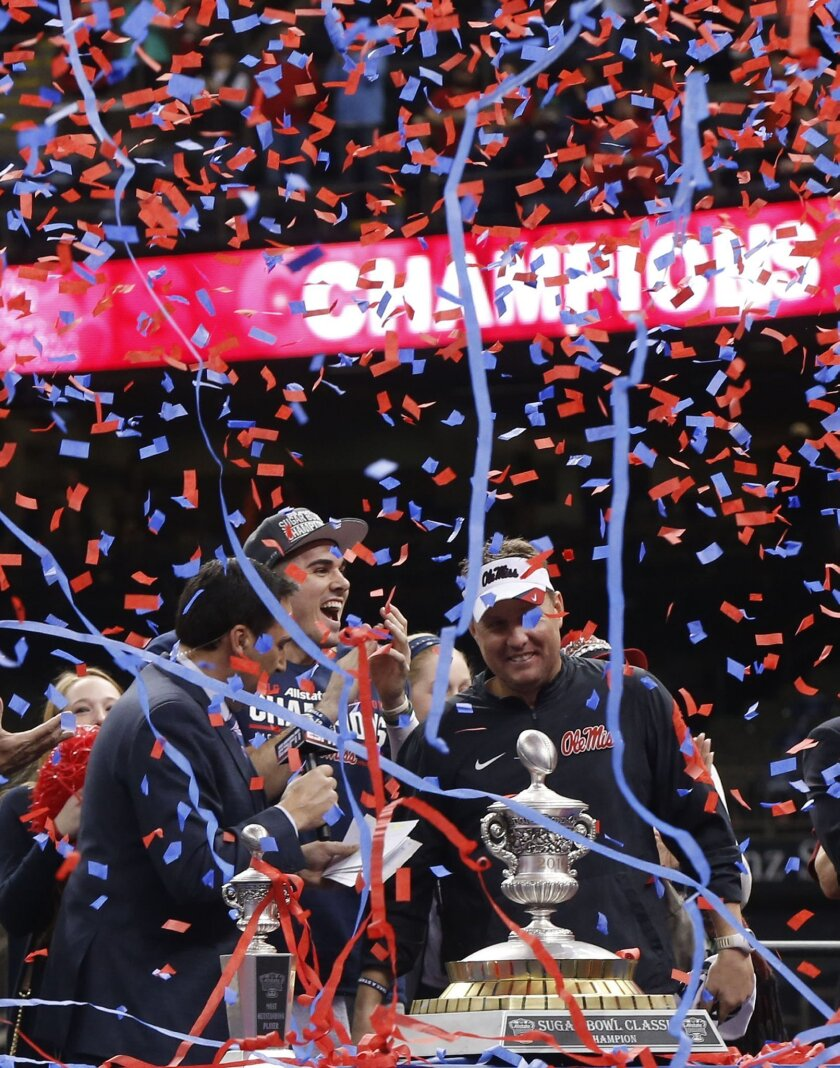 Mississippi quarterback Chad Kelly, center, and head coach Hugh Freeze celebrate as confetti rains down after the Sugar Bowl college football game against Oklahoma State in New Orleans, Friday, Jan. 1, 2016. Mississippi won 48-20. (AP Photo/Bill Feig)