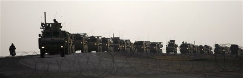 A motorcycle drives past a large US Army vehicle convoy near the town of Maidan Shar, Wardak province, Afghanistan, Monday Nov. 30, 2009. (AP Photo/Dario Lopez-Mills)
