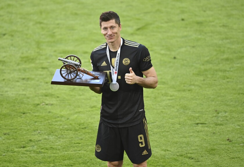 Bayern's Robert Lewandowski holds a trophy of the best scorer of the season after winning the Bundesliga title after the German Bundesliga soccer match between Bayern Munich and FC Augsburg at the Allianz Arena stadium in Munich, Germany, Saturday, May 22, 2021. (Sven Hoppe, Pool via AP)