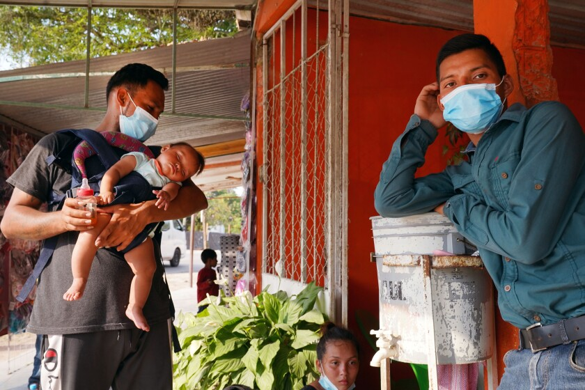 Honduran migrants, including one holding a baby, wait outside