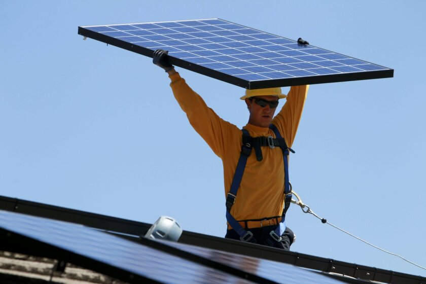 Lead installer for Sullivan Solar Power Mike DeCarl carries a solar panel while he and a crew install solar panels on the roof of a home in Carlsbad on Wednesday.