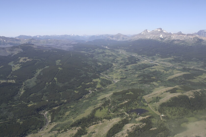 FILE - This June 16, 2015, aerial file photo, shows the Badger-Two Medicine area near the Blackfeet Indian Reservation and Glacier National Park, rear, in Montana. President Donald Trump's public lands steward, acting U.S. Bureau of Land Management Director William Perry Pendley, has recused himself from dealings with a company seeking to drill in the Badger-Two Medicine following criticism from U.S. Sen. Jon Tester and environmentalists. (Tristan Scott/Flathead Beacon via AP, File)
