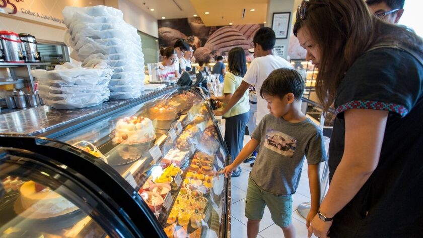 Julian Lai, 8, and his mom, Fiona Kwei, look at the pastries at 85°C Bakery Cafe at Diamond Jamboree.