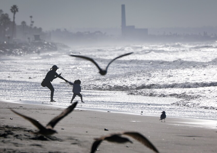 With the Encina Power Station in the background, Damaris Sanchez, left, of Oceanside, records the moments, as a playful Maya Fierro, 3, right, her boyfriend's daughter, also of Oceanside, tries to pull her into the ocean near the Oceanside Pier, January 29, 2020 in Oceanside, California.