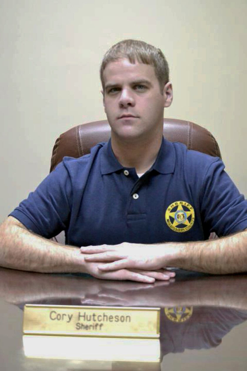 FILE - In this undated file photo, then Mississippi County Sheriff Cory Hutcheson sits behind his desk at the Mississippi County Detention Center in Charleston, Mo. A southeastern Missouri city has agreed to pay $500,000 to settle its part in a lawsuit brought by the family of a Black man who died in jail after having his neck pinned down for several minutes by the knee of Hutcheson in 2017. Hutcheson was accused of pressing his knee against Sanders' neck for up to three minutes. (Leonna Heuring/Sikeston Standard Democrat via AP, File)