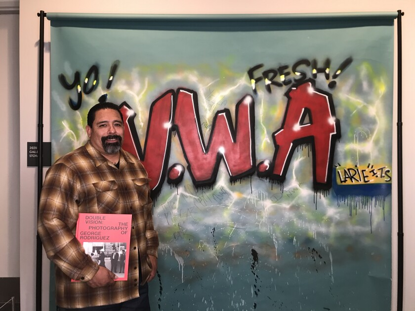Larry Ruedas Jr. — once known as LARIE — stands in front of a graffiti backdrop he painted for N.W.A.