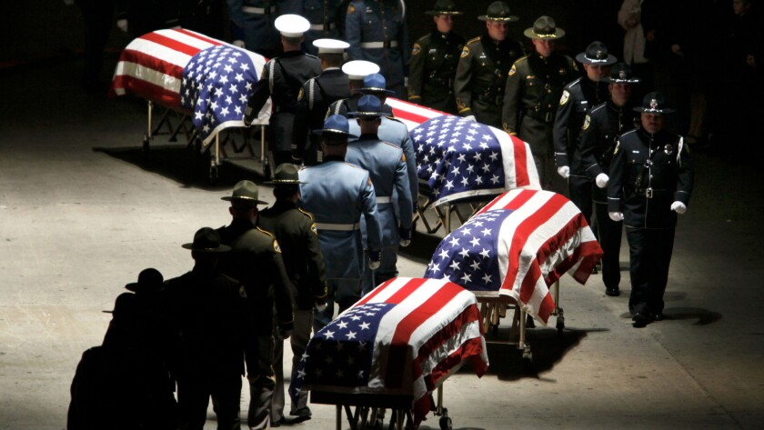 Law enforcement officers approach the caskets of four Lakewood, Wash., police officers who were gunned down in a coffee shop before the start of their shift in 2009.
