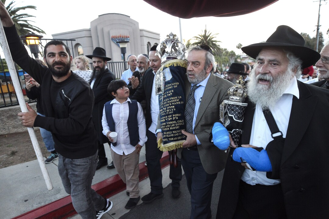 Howard Kaye, center, husband of Lori Gilbert-Kaye, carries the new torah dedicated to his wife as Rabbi Yisarel Goldstein, right, and other members of the Chabad of Poway synagogue celebrate the completion on Wednesday, May 22, 2019 in Poway, California.