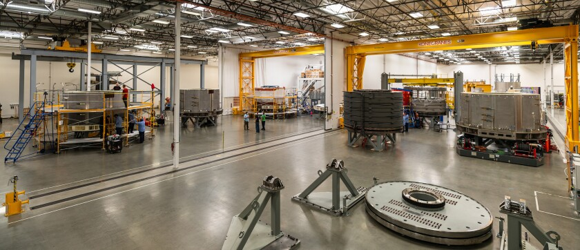 Six ITER Central Solenoid modules at various stages of fabrication at General Atomics' Magnet Technologies Center in Poway.