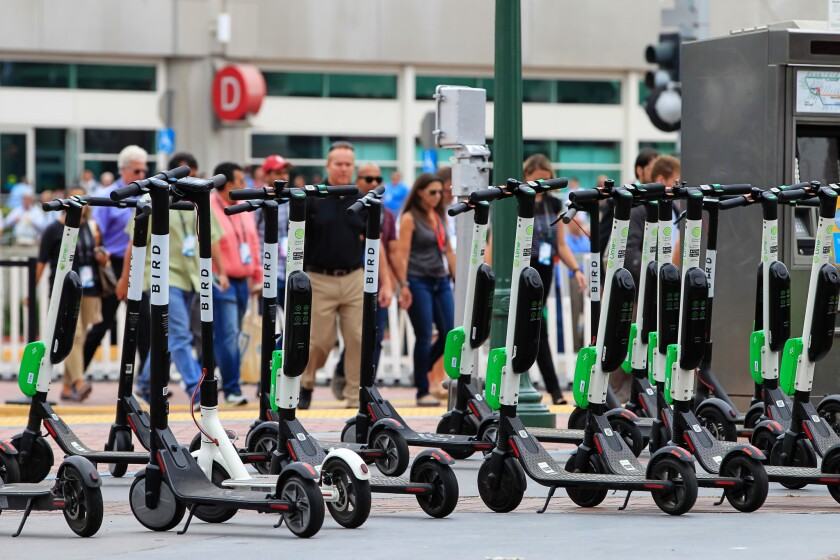 A large number of rental scooters are parked near the San Diego Convention Center along 5th Avenue in July 2018.
