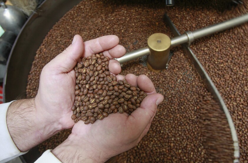Head roaster Nick Berardi makes a heart with roasted Guatemalan coffee beans at the Mostra warehouse in Carmel Mountain area.