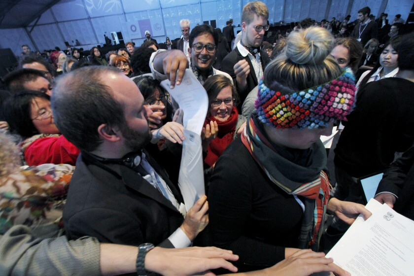 """Delegates receive copies of the document dubbed """"The Lima Call for Climate Action"""" after its approval during the plenary session of the 20th U.N. Climate Change Conference in Lima, Peru."""