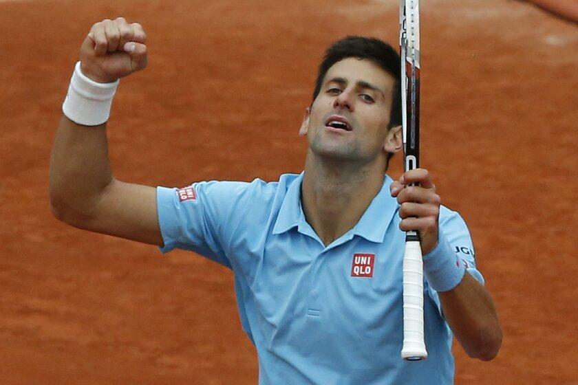 Serbia's Novak Djokovic celebrates winning the fourth round match of the French Open tennis tournament against France's Jo-Wilfried Tsonga at the Roland Garros stadium, in Paris, France, Sunday, June 1, 2014. Djokovic won in three sets 6-1, 6-4, 6-1. (AP Photo/Michel Euler)