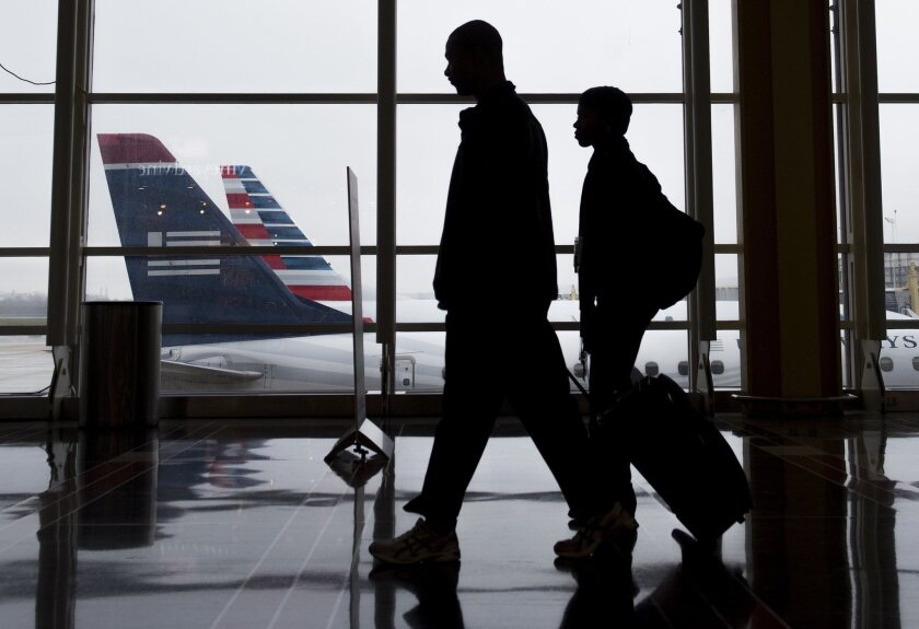 Passengers walk through the terminal as they head to their flights at Reagan National Airport in Arlington, Va., on Dec. 23, 2015. Three of the nation's biggest carriers were sued by travel agents who accuse the airlines of conspiring to keep fares high on multi-city trips.