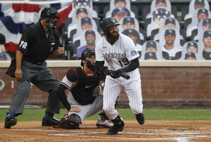 Colorado Rockies' Charlie Blackmon, front, follows the flight of his single as he breaks from the batter's box as Arizona Diamondbacks catcher Carson Kelly, back right, and home plate umpire Alfonso Marquez look on in the first inning of a baseball game Tuesday, Aug. 11, 2020, in Denver. (AP Photo/David Zalubowski)