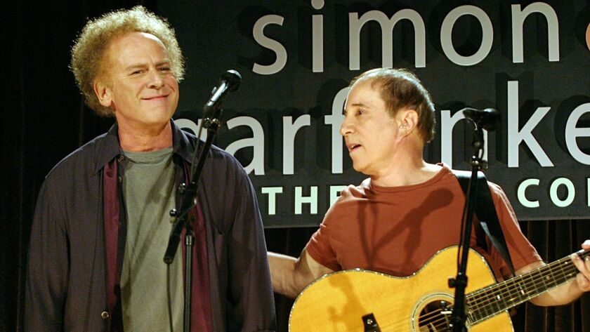 Paul Simon, right, places his hand on the shoulder of former partner Art Garfunkel as they perform d