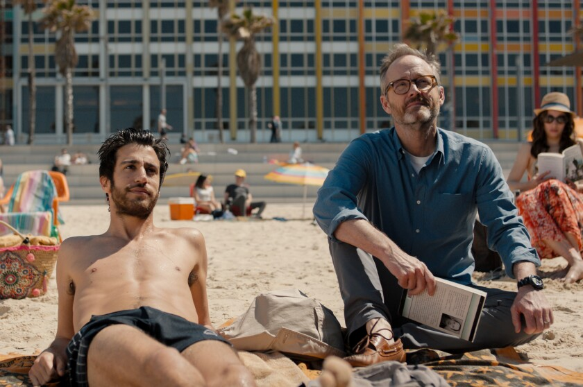 Niv Nissim, left, in swimsuit, and John Benjamin Hickey, in street clothes, sit on the beach