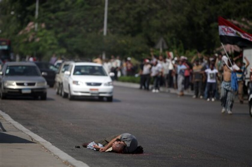 """A man lies dead after being shot by Egyptian troops in Cairo, Egypt, Friday, July 5, 2013. Egyptian troops opened fire on mostly Islamist protesters marching on a Republican Guard headquarters Friday to demand the restoration of ousted President Mohammed Morsi, killing at least one. The shooting came as tens of thousands of his supporters chanting """"down with military rule"""" rallied around the country. (AP Photo/Khalil Hamra)"""