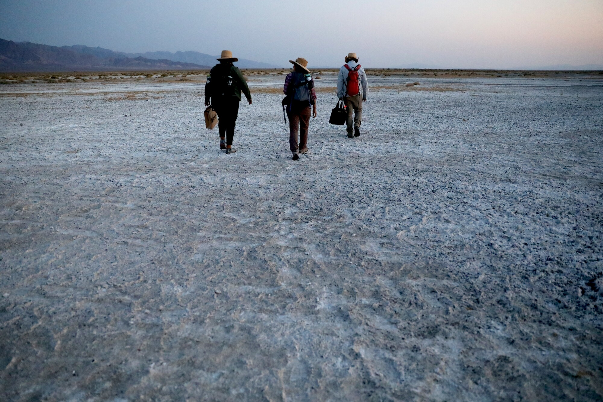 Three people trudge over a craggy desert plain