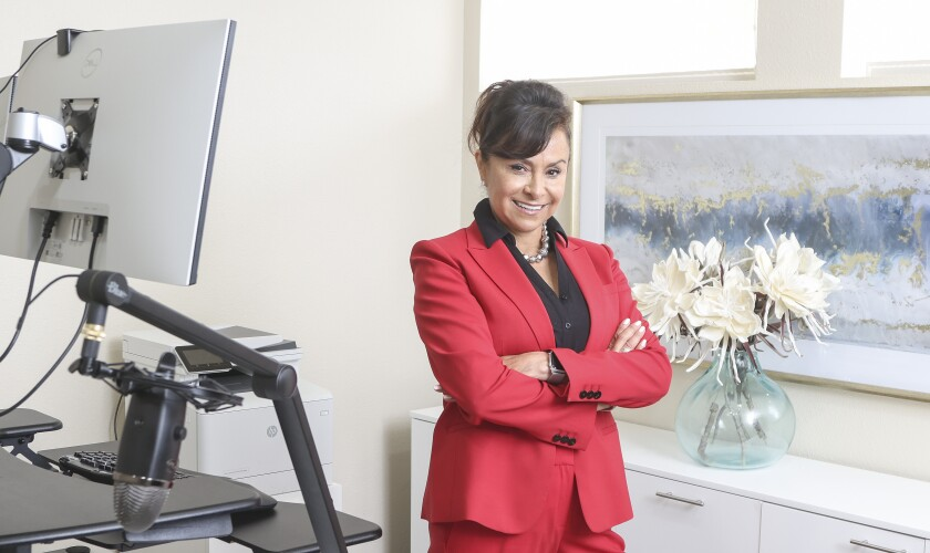 Marina Araiza stands in an office, wearing a red suit and smiling at the camera