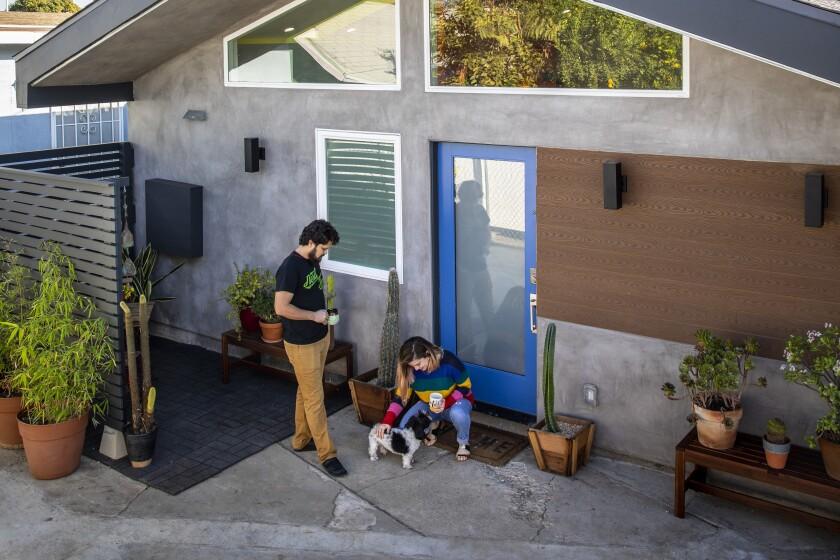 John Velasco and Ariel Gomez-Hernandez, with their dog Lando, outside their East L.A. ADU.