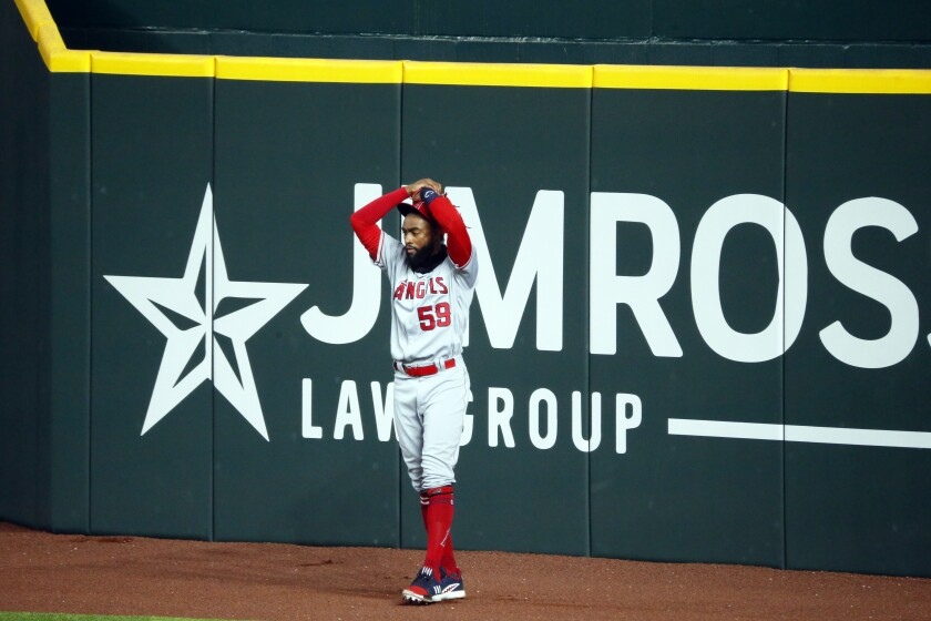 The Angels' Jo Adell puts his hands on his head after a fly ball by Texas Rangers' Nick Solak popped out of his glove.