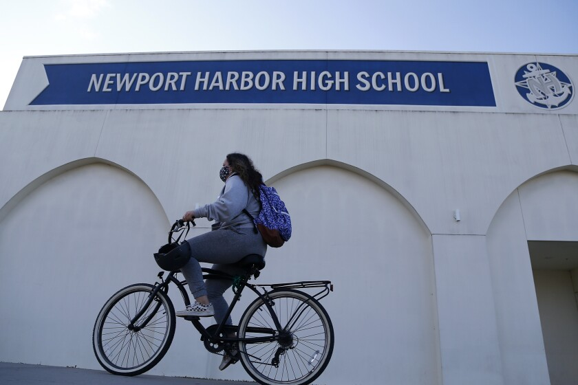 A student rides her bicycle in front of Newport Harbor High School.