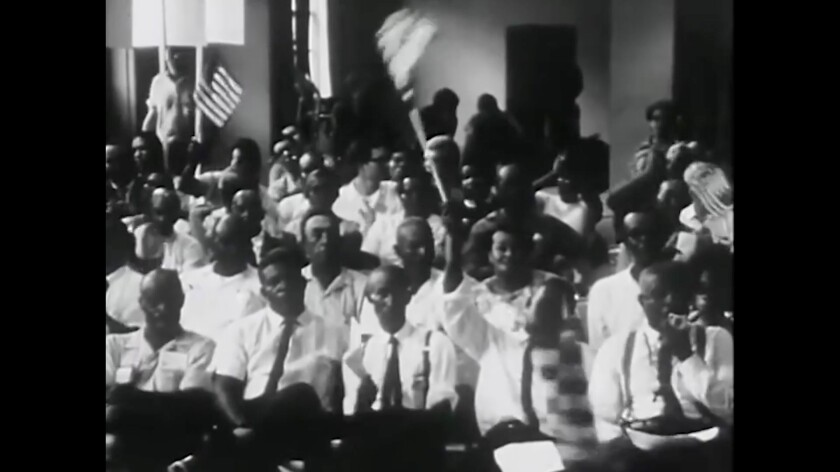 A black-and-white image from video shows a group of Black people in white shirts people waving flags.