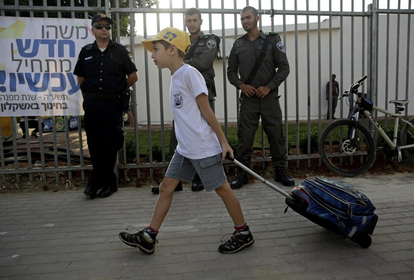 An Israeli student pulls his bag on his way to elementary school as he walks past policemen in the costal city of Ashkelon, Monday, Sep. 1, 2014. Thousands of children in southern Israel return to school Monday after spending the summer vacation in bomb shelters taking cover from the thousands of Palestinian rockets and mortars fired from Gaza during 50 days of war. (AP Photo/Tsafrir Abayov)
