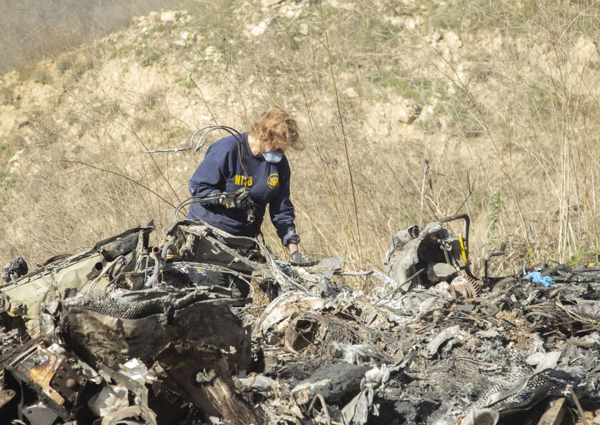 National Transportation Safety Board investigator Carol Hogan on Monday examines the wreckage