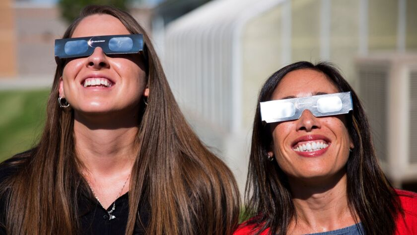 Two science teachers in the Twin Falls, Idaho, school district -- which bought 11,000 pairs of solar glasses for viewing the Aug. 21 eclipse -- use their shades to look at the sun on July 18.