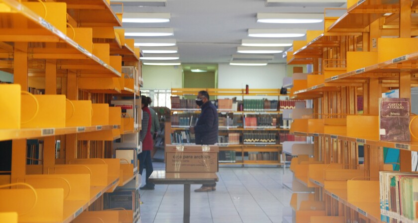 Shelves look empty as employees arrange books in boxes at the Benito Juárez library in Tijuana on 22 February.
