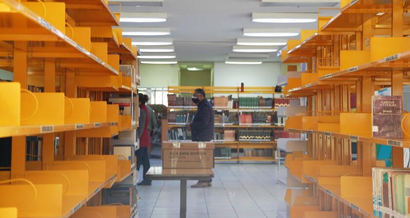 Estantes lucen vacíos mientras los empleados acomodan libros en cajas