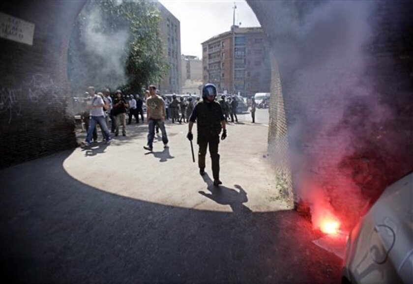 An Italian police officer in anti-riot gear goes to put out a flare after university students clashed with police, following a spontaneous demonstration at a Rome university against the upcoming G8 (Group of Eight) summit, scheduled for July 8-10 in L'Aquila, Tuesday, July 7, 2009. (AP Photo/Francesco Benvenuti)