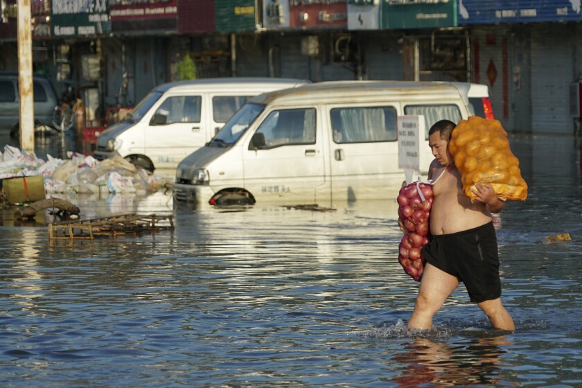 A man carrying sacks of food walks through a street flooded to his knees in China.