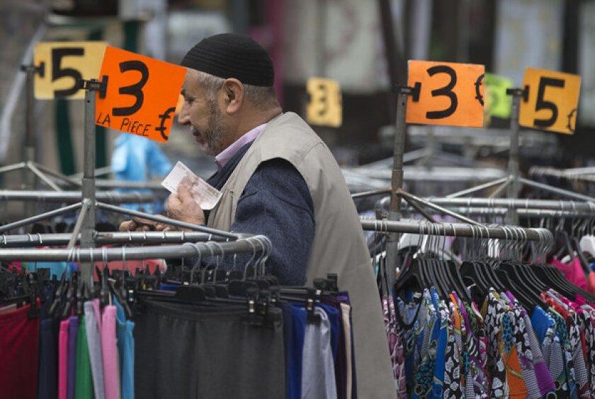 A man shops in a Paris market.