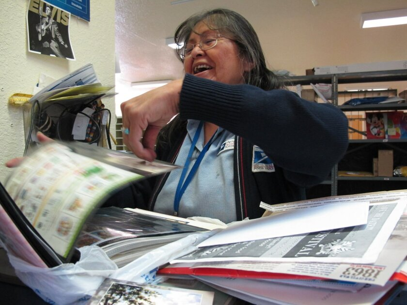 Marie Howard, flips through scrapbooks Tuesday, March 22, 2016 in Cameron, Ariz. Howard says the clippings remind her of when Democratic presidential candidate Hillary Clinton visited the Navajo Nation and the Grand Canyon long before she became a presidential contender. (AP Photo/Felicia Fonseca)