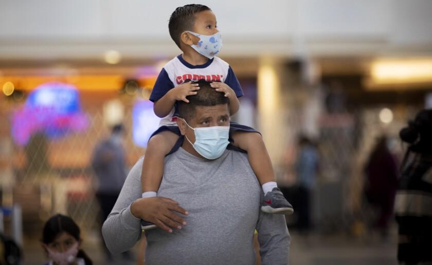 Mario Tejada carries his son Mario Tejada Jr., 3, on his shoulders at Los Angeles International Airport on Tuesday.