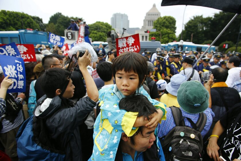 In this photo taken on Sunday, Aug. 30, 2015, a father carries his son on his shoulders during a rally in front of the parliament building in Tokyo. Mothers holding their children's hands stood in the sprinkling rain, some carrying anti-war placards, while students chanted slogans to the beat of a drum against Prime Minister Shinzo Abe and his defense policies. (AP Photo/Shizuo Kambayashi)