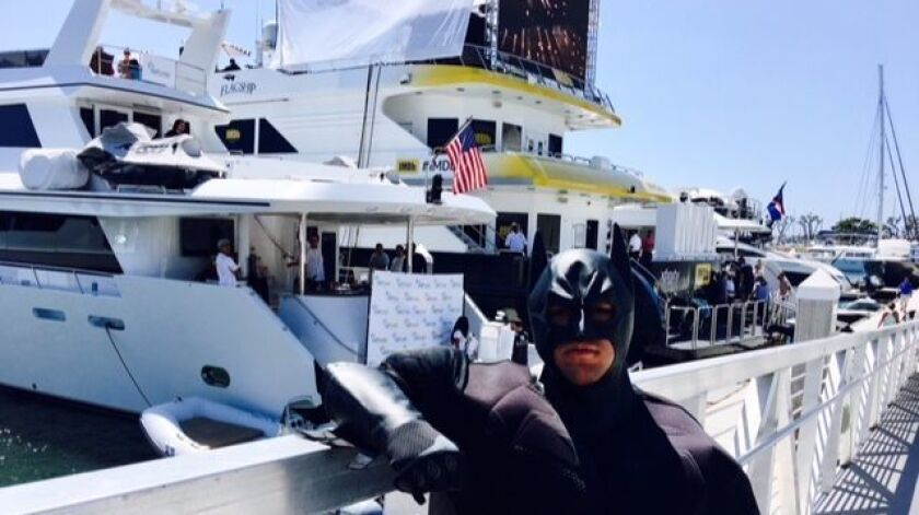 Over the shoulder of the Comic-Con Batman figure is the marijuana marketing Budtrader yacht behind t