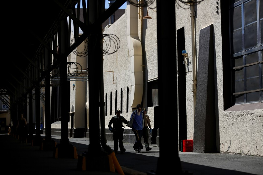 Three people walk next to a big building inside San Quentin State Prison.