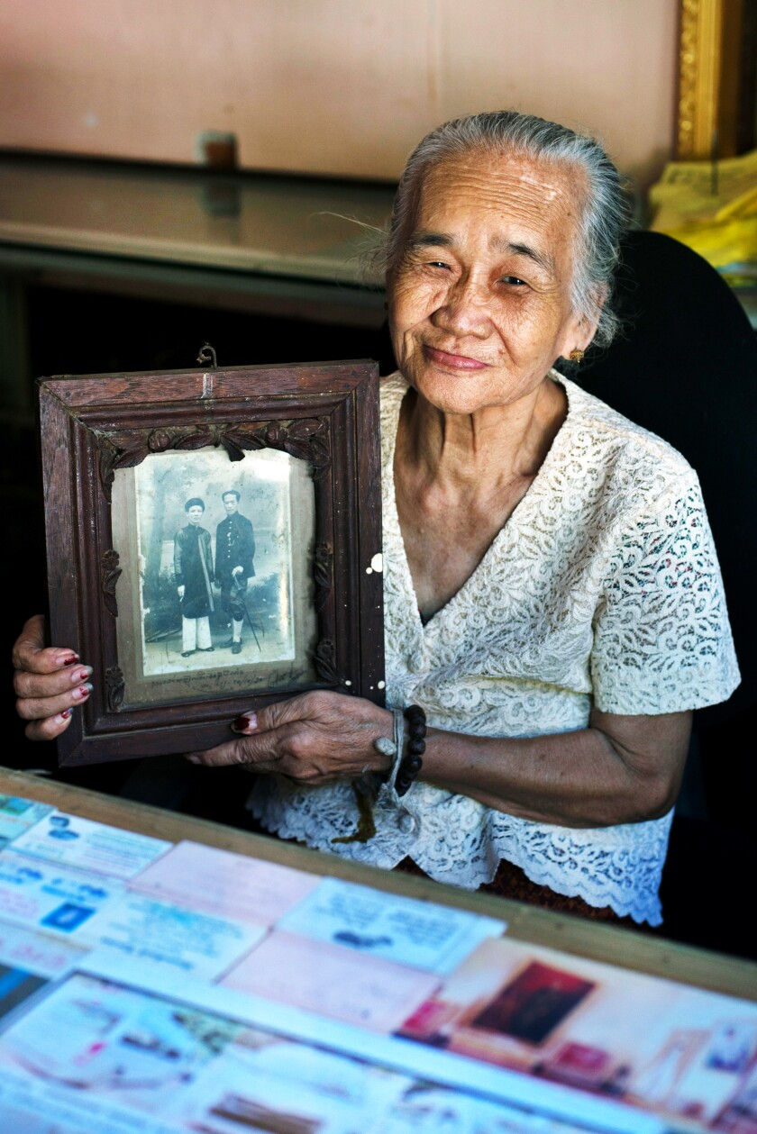 Chanthanom Chaleunsinh holds a portrait of her father, Phia Sing