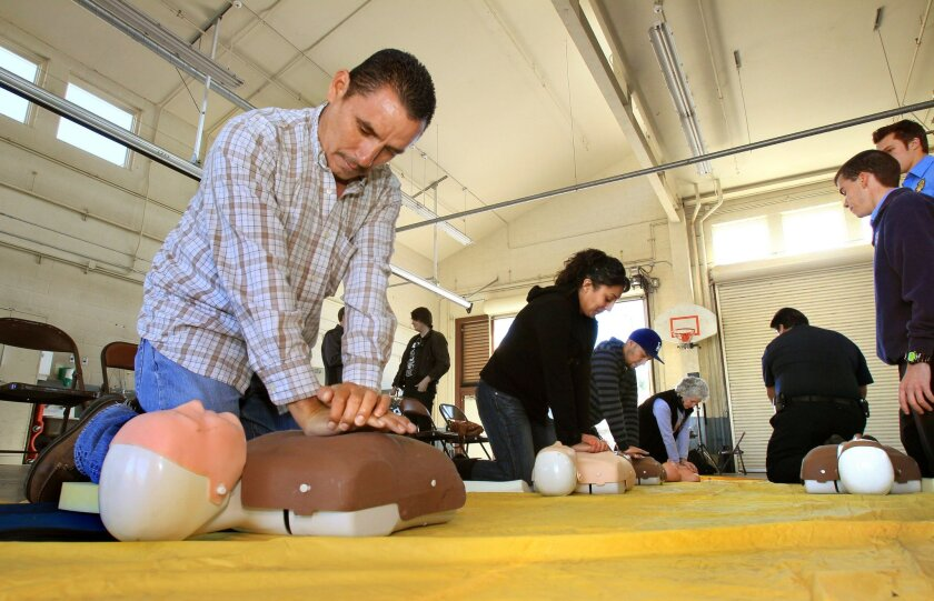 CPR student Macario De La Torre, left, and others at right, press on the chest of practice mannequins as they learn proper CPR technique during a class at Murrieta Fire Station No. 2.