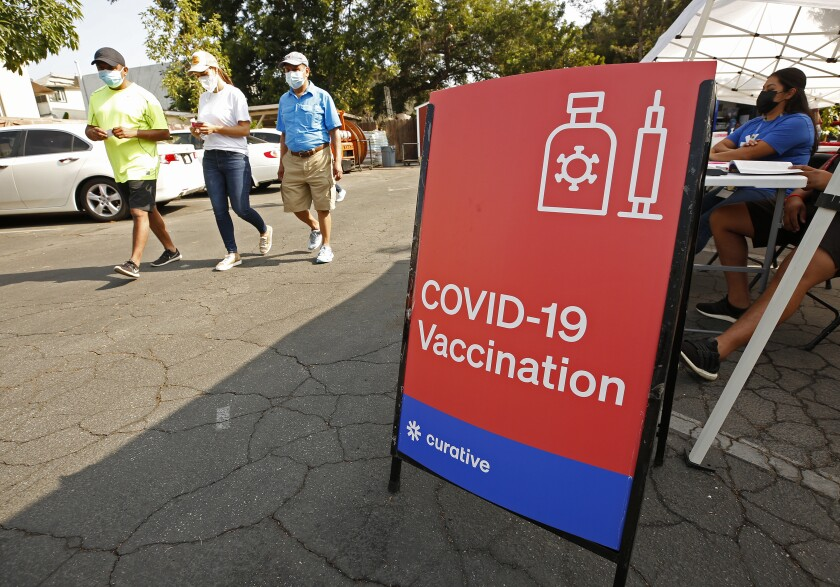 Three family members leave a COVID-19 vaccine clinic in Los Angeles after getting immunized.