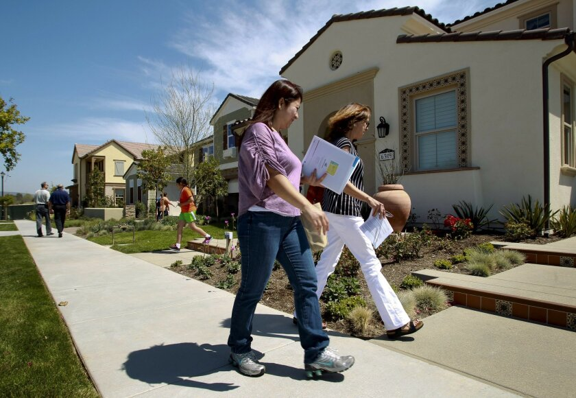 Grace Reyno, left, and Terry Filice walk past a model home as they and other people browse through the model homes at a Pardee Homes community in Carmel Valley in the spring.