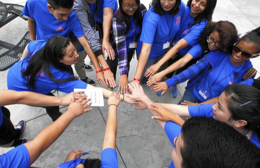 Group leader Sandy Ghoubrial, left, leads incoming freshmen in the Summer Bridge program in a cheer before heading off on a tour of the California State Fullerton campus.