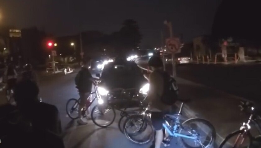 Critical Mass bicyclists in front of a vehicle.
