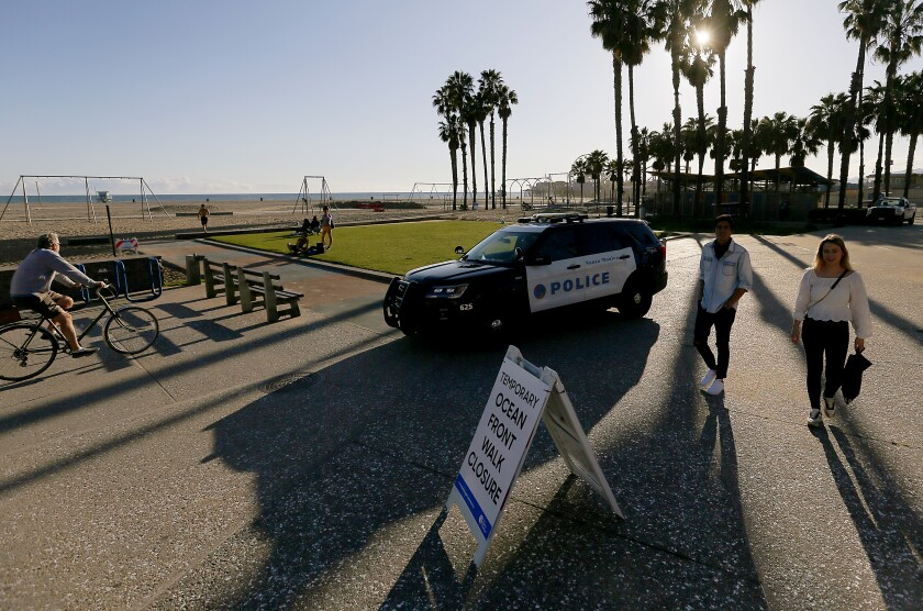 An officer in a police cruiser tells beachgoers Saturday to clear the oceanfront area in Santa Monica, which is closed to enforce social distancing because of the coronavirus pandemic.