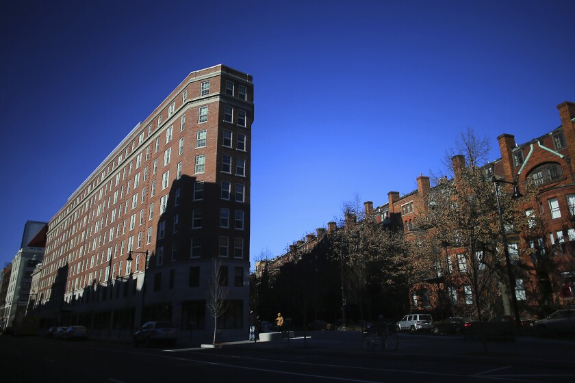 FILE - In this Jan. 17, 2019 file photo, Boston University's Myles Standish Hall dormitory, left, is partially covered in shadow in Boston. THe Massachusett Tribe at Ponkapoag is calling on BU to change the name of the dorm that honors Myles Standish, the military leader of the Pilgrims. The tribe says Myles Standish Hall should be renamed Wituwamat Memorial Hall after a leading Native American figure massacred with other tribal members by Plymouth Colony settlers in 1623. (Lane Turner/The Boston Globe via AP, File)