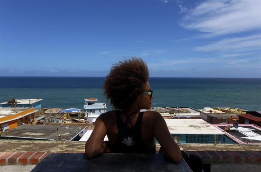 Una lugareña observa desde lo alto el barrio costero y popular La Perla en San Juan, Puerto Rico. EFE/Archivo